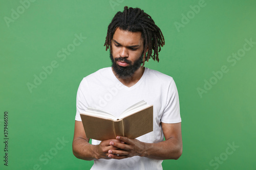 Pensive concentrated young african american man guy with dreadlocks 20s wearing white casual t-shirt posing holding in hands reading book studying isolated on green color background studio portrait Fototapeta