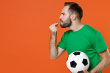 Young Man Football Fan In Green T-shirt Cheer Up Support Favorite Team With Soccer Ball Blowing In Whistle Looking Aside Isolated On Orange Background Studio. People Sport Leisure Lifestyle Concept.