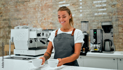 Fototapeta Young attractive female barista stands at the counter in a coffee shop and smiles, serving cups of prepared coffee to a customer. obraz