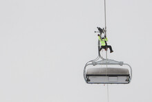 Heroes Rescue Teams On A Chairlift At Ski Resort On The Dolomites. Emergency Rescue Passengers With The Use Of Ropes And Safety Ladders In Bad Weather Winter Conditions. Foggy Day.