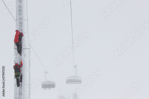 Fototapeta Heroes rescue teams on a chairlift at ski resort on the Dolomites