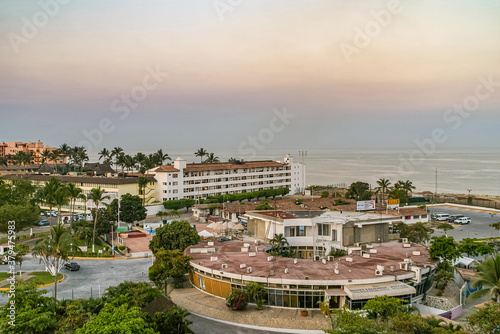 Photo Puerto Vallarta, Mexico - April 25, 2008: Morning yellow-orange light over ocean with circular port authority offices up front on harbor