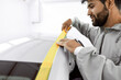 canvas print picture - mechanic caucasian man with yellow paper tape plasters car for polishing it, paint and varnish, remove scratches in a vehicle wash and detailing workshop.