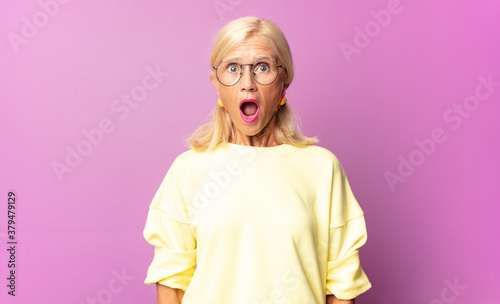Fototapeta middle age woman looking very shocked or surprised, staring with open mouth saying wow obraz
