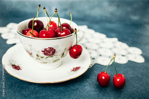 Photo Red cherries in an old porcelain cup on the table with crochet under it