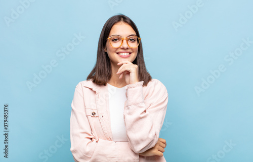 young pretty woman looking happy and smiling with hand on chin, wondering or asking a question, comparing options