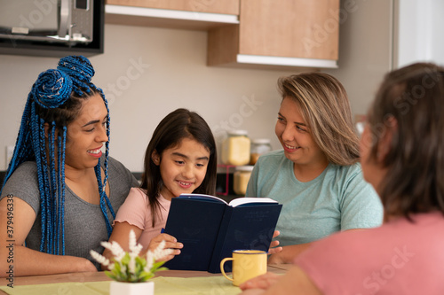 Cheerful brazilian young child with book reading to her mothers at kitchen table, inside Wallpaper Mural