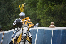 Knight With Lance And Black-and-yellow Shield On A Running White Horse During Jousting At Late Middle Ages Tournament Reenactment