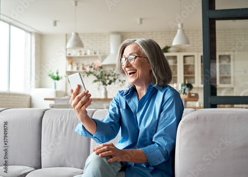 Foto Happy mature old 60s woman holding smartphone using mobile phone app for video call, laughing while watching funny video, feeling excited winning online lottery bid on cellphone sits on couch at home