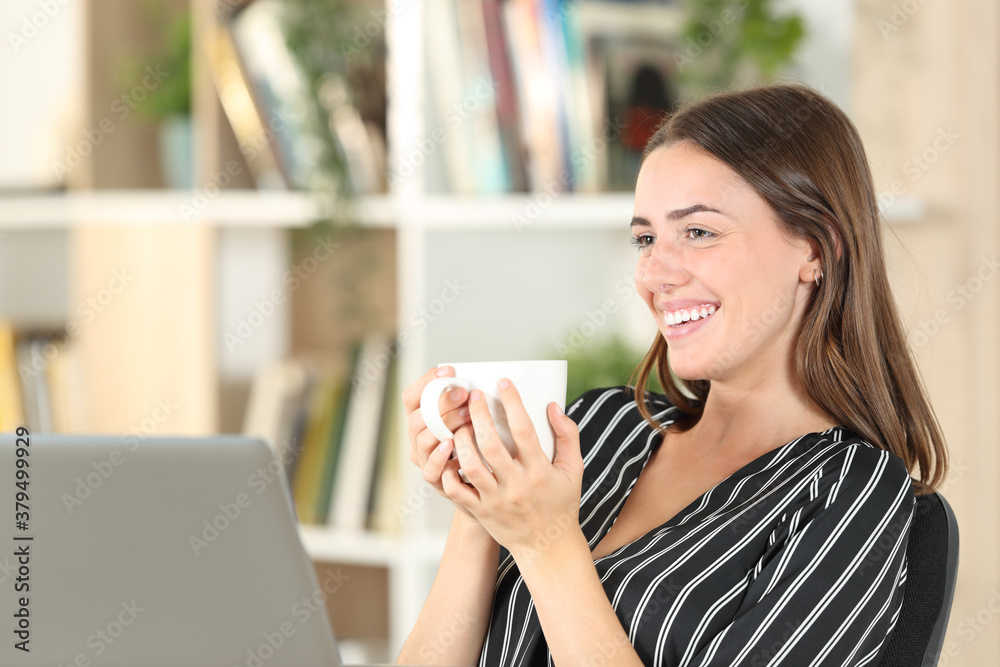 Fototapeta Happy woman drinking coffee looks away at home