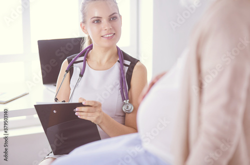 Young woman doctor with stethoscope and tablet speaking with pregnant woman at hospital Wallpaper Mural