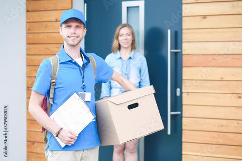 Tela Smiling delivery man in blue uniform delivering parcel box to recipient - courier service concept