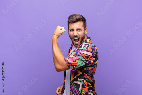 Photo young man feeling happy, satisfied and powerful, flexing fit and muscular biceps