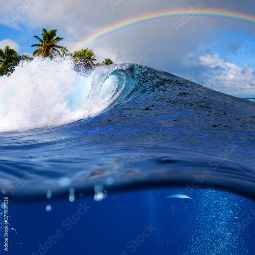Fototapeta Perfect tropical ocean view splitted by waterline to two part. Shorebreak  breaking surfing wave. Palms and clouds in daylight with colorful rainbow. obraz