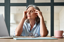 Tired Stressed Old Mature Business Woman Suffering From Headache At Work. Upset Sick Senior Middle Aged Lady Massaging Head Feeling Migraine From Overwork Or Menopause Using Computer At Home Office.