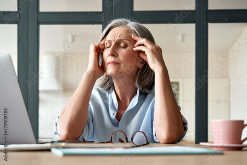 Fotografía Tired stressed old mature business woman suffering from headache at work