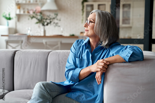 Calm relaxed mature older woman relaxing sitting on couch at home. Peaceful middle aged grey-haired lady resting on sofa in modern living room enjoying lounge and no stress, looking away, thinking.