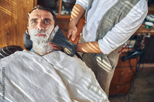 Photo Concerned client of a barbershop being shaved with an axe