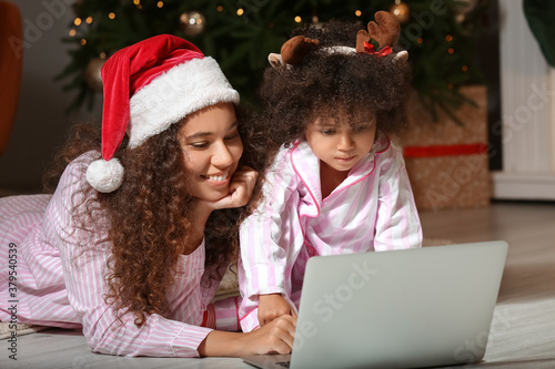 Obraz na plátně Cute African-American girl and her mother with laptop at home on Christmas eve