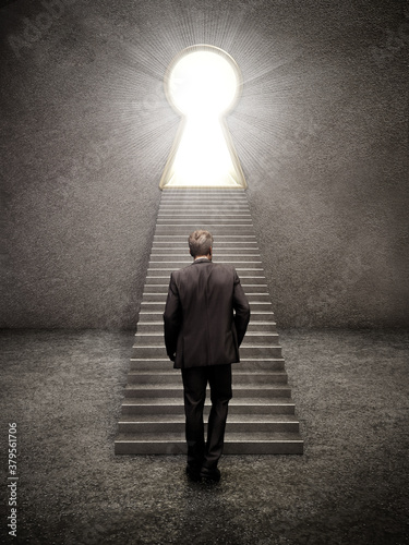 Obraz na plátně Businessman standing in front of the ladders leading to the bright keyhole