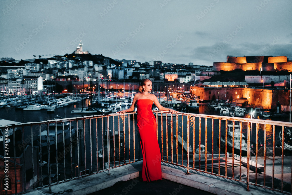 Fototapeta An elegant girl in a red evening dress on the streets of the night city of Marseille.A woman in a red evening dress in France