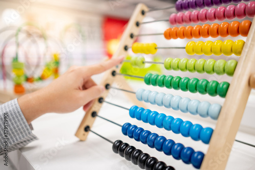 Fototapeta Male hand calculating with beads on wooden rainbow abacus for number calculation. Mathematics learning concept obraz