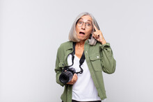 Middle Age Woman Looking Surprised, Open-mouthed, Shocked, Realizing A New Thought, Idea Or Concept. Photographer Concept