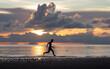 Persona corriendo por la playa con atardecer de fondo