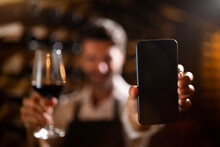Modern Farmer Or Winemaker Is Showing In Camera A Smartphone With Blank Winery Online Commerce Applications For Checking Customer Service And Selling Orders Summary Of Wine Production In A Wine Cellar