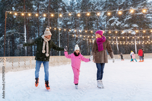 Obraz na plátně christmas, family and leisure concept - happy mother, father and daughter at out