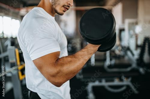 Obraz Muscular man, focus on biceps, strong arm. - fototapety do salonu