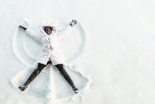 Black Girl In Fur Coat And High Top Boots Lies On White Glade And Draws Snow Angel Picture With Arms And Legs Top View