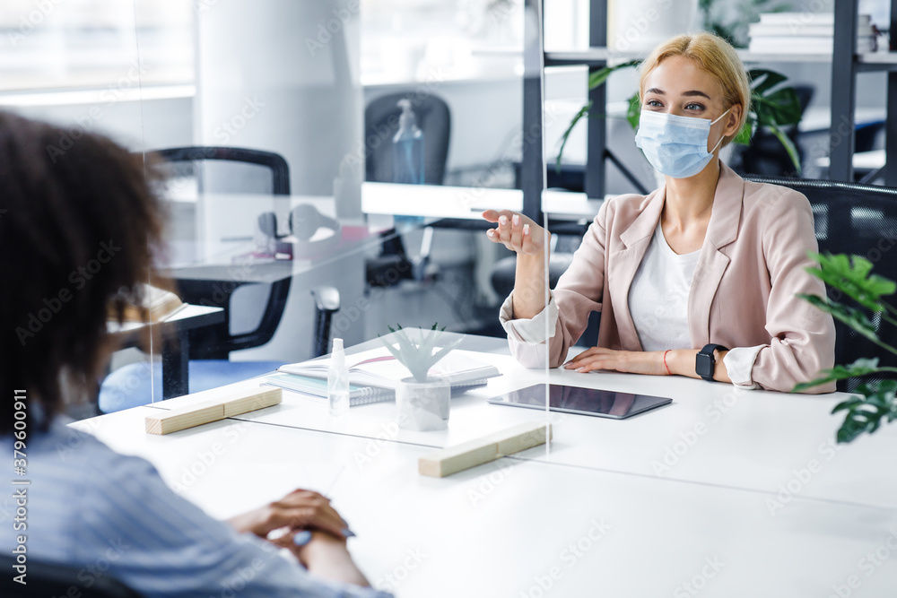 Fototapeta African american lady speaks to business woman in protective mask through glass partition in office interior