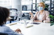 African american lady speaks to business woman in protective mask through glass partition in office interior