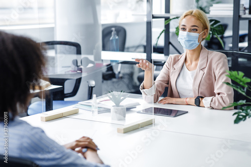Fototapeta African american lady speaks to business woman in protective mask through glass partition in office interior obraz