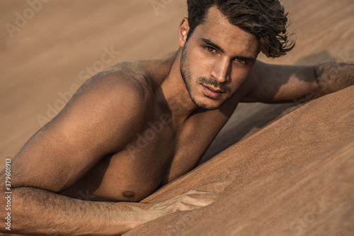 Tablou Canvas Portrait of sexy handsome shirtless male model on the desert sand dunes