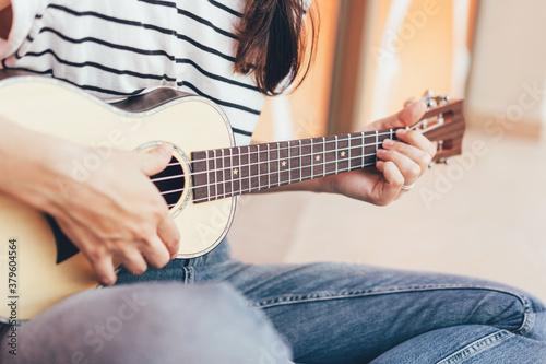 Obraz na plátně Woman play a song on ukulele,  close-up musical instrument.