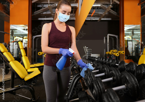 Fototapeta premium Woman cleaning dumbbells with disinfectant spray and cloth in gym