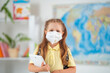little schoolgirl in a protective mask with a backpack during the coronavirus.