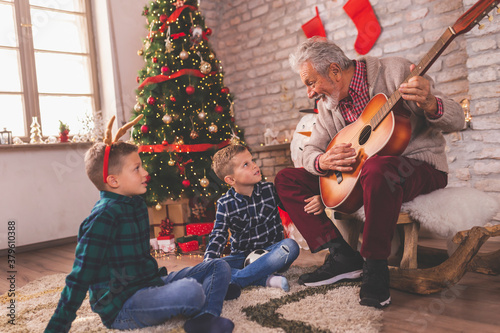 Obraz na plátně Grandfather and grandchildren playing the guitar and singing Christmas songs
