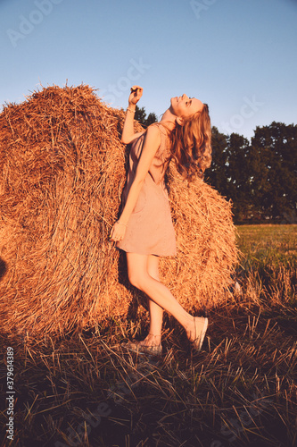 Portrait of young sexy woman with red hair on the haystack in motning sunlight, countryside Canvas Print