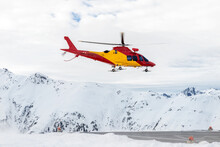Mountain Ski Life Rescue Medic Helicopter Taking-off From Station Helipad To Search Injured Skiers And Help At Accident. Emergency Chopper At Austrian Alpine Skiing Resort. Alps Landsape