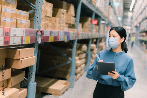 Young smart Asian business working woman wear surgical mask  using digital tablet to check goods on shelves for inventory management  in warehouse, Logistics business planning concept with copy space