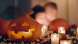 canvas print picture - Carved Halloween pumpkin lantern on table with burning candles and sweets in decorated home
