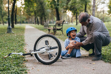 Boy Fall From His Bike In The Park. Grandfather Helping Him