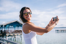 Happy Adult Woman Photographing With Smartphone On Pier