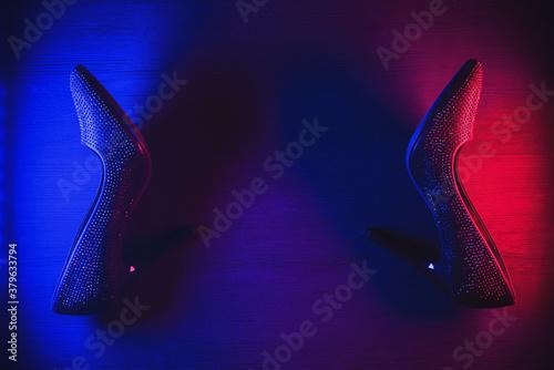 Fototapeta Black high heels shoes in the neon lights on black background. obraz