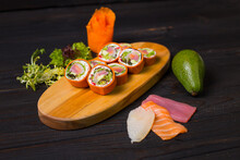 Close Up Of Japanese Sushi Roll Without Rice With Raw Salmon, Tuna And Haddock Fillet, Salad Mix, Cream Cheese In Carrot Slices Served On Wooden Board Plate. Ingredients Near Pan Asian No Rice Dish