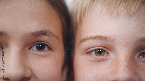 Close up portrait of brunette girl and blond boy children eyes looking at camera