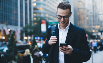 Businessman smiling while using phone on street
